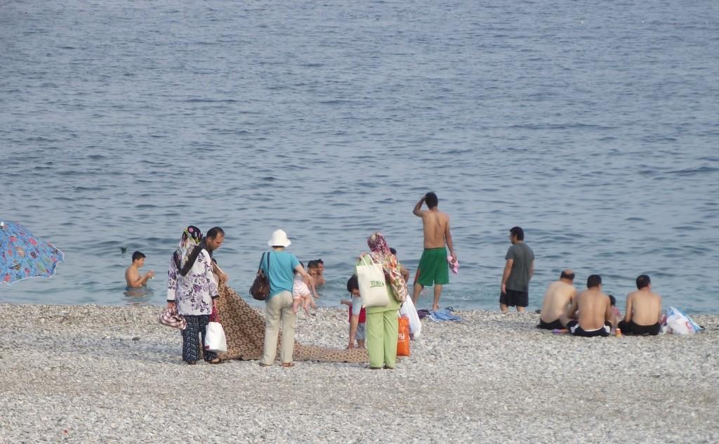 Turecká rodina na pláži: koberec a všetko potrebné v igelitkách.