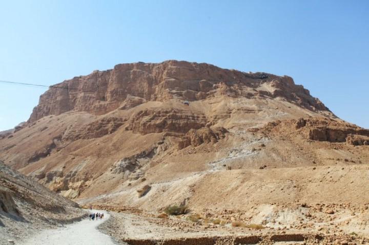 Massada. Pohľad od Mŕtveho mora. Pevnosť na jej vrchu bola vybudovaná v 1. storočí pred Kristom kráľom Herodotom. Slúžila ako vojenská pevnosť počas prvej židovskej vojny. Po dobití Rimanmi jej 1000 obrancov spáchalo samovraždu. Pevnosť je dôležitá súčasť židovskej kultúry