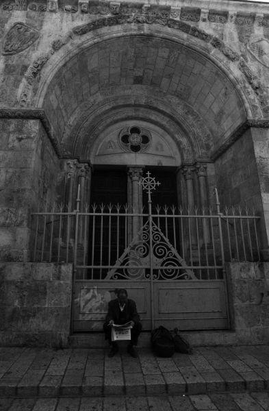 Muž čítajúci noviny pri jednom z desiatok kostolov v centre Jeruzalema
